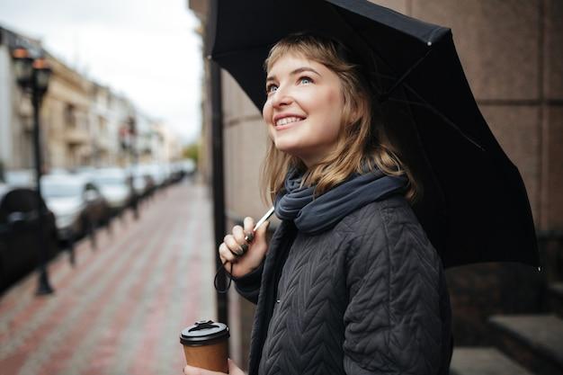 Portret van jonge glimlachende dame die zich op straat met zwarte paraplu en koffie in handen bevindt en gelukkig opzij kijkt