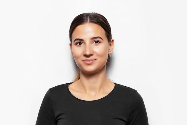 Portret van jonge glimlachende donkerbruine vrouw.