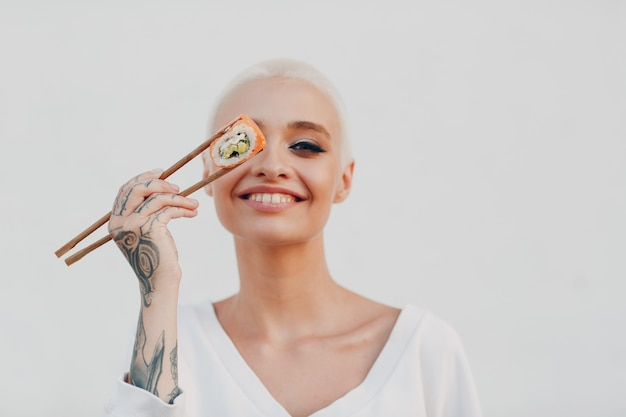 Portret van jonge glimlachende millenial europese kortharige vrouw die sushi philadelphia zalm rol eet...