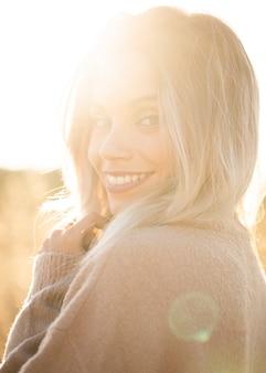 Portret van jonge glimlachende vrouw die in zonlicht camera bekijken