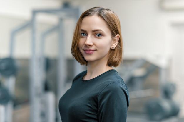 Portret van jonge glimlachende vrouw in de gymnastiek