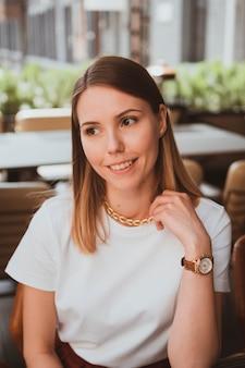 Portret van jonge glimlachende vrouw in een straatcafé