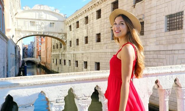 Portret van jonge glimlachende vrouw in rode kleding en hoed met brug der zuchten van venetië
