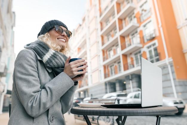 Portret van jonge glimlachende vrouw in warme kleren