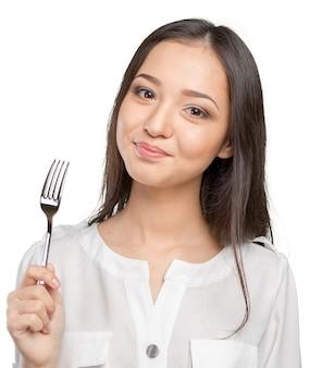Portret van jonge glimlachende vrouw met vork in haar mond
