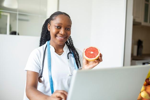 Portret van jonge glimlachende vrouwelijke voedingsdeskundige in de spreekkamer. voedingsdeskundige bureau met gezond fruit, sap en meetlint. diëtist die aan dieetplan werkt.