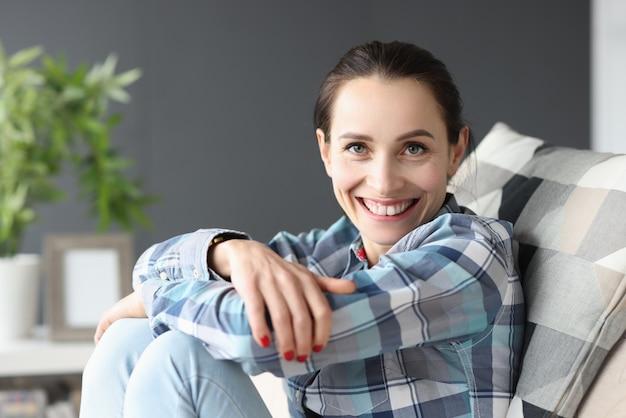Portret van jonge glimlachende vrouwenzitting op bank