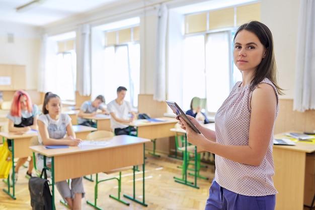 Portret van jonge glimlachende zelfverzekerde vrouwelijke leraar met digitale tablet in de klas met leerlingen die naar de camera kijken. onderwijs, school, universiteit, onderwijsconcept