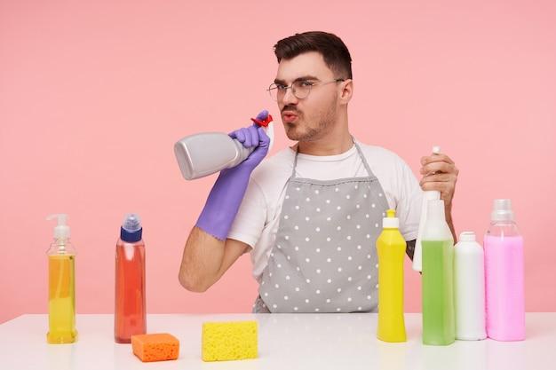 Portret van jonge grappige bruinharige man met bril gekleed in werkkleding en rubberen handschoenen blaast op een spuitfles in zijn hand terwijl hij er een pistool mee imiteert, geïsoleerd op roze