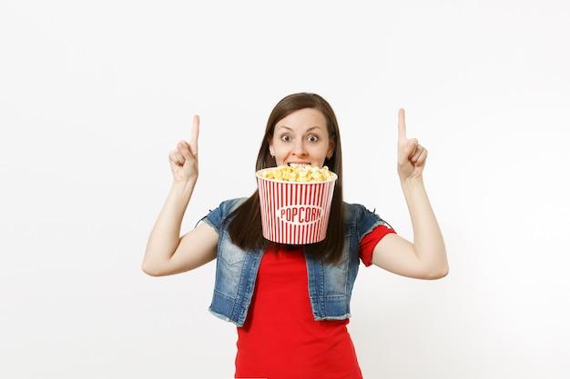 Portret van jonge grappige mooie vrouw in casual kleding kijken naar film film, houden in tanden emmer popcorn, wijsvingers omhoog wijzend op kopie ruimte geïsoleerd op een witte achtergrond. emoties in de bioscoop