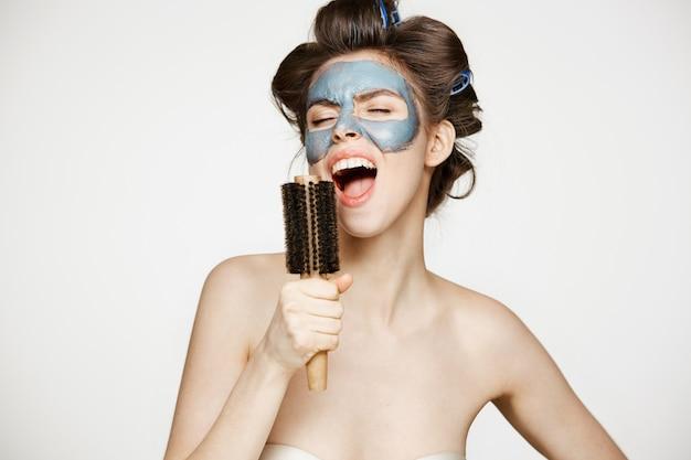 Portret van jonge grappige vrouw in haarkrulspelden en gezichtsmasker zingen in kam. schoonheid en huidverzorging concept.