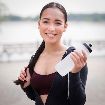 Portret van jonge het waterfles van de vrouwenholding