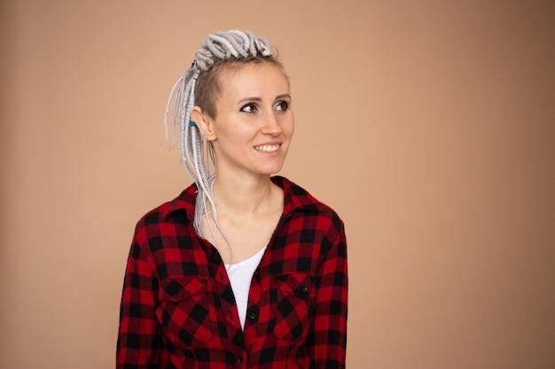 Portret van jonge hipster vrouw met dreadlocks geïsoleerd op beige