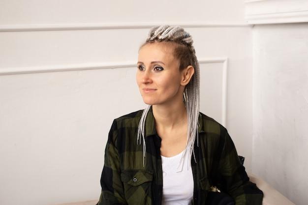 Portret van jonge hipster vrouw met dreadlocks thuis