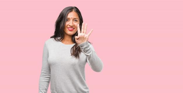 Portret van jonge indiase vrouw toont het nummer vier, symbool van het tellen