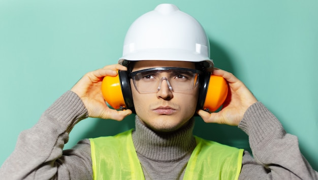 Portret van jonge ingenieur bouwvakker veiligheidshelm, bril, jas en koptelefoon dragen op achtergrond van aqua menthe kleur.