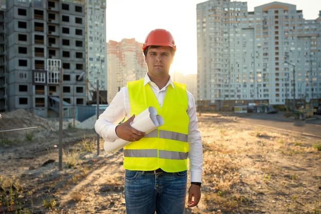 Portret van jonge ingenieur poseren met blauwdrukken tegen bouwplaats against