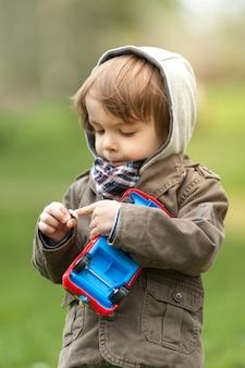 Portret van jonge jongen die een bloem controleert