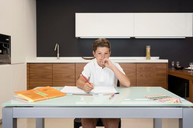 Portret van jonge jongen die zijn huiswerk doet