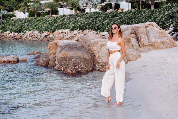 Portret van jonge kalme gelukkig kaukasische fit slanke vrouw in crop cami top en broek alleen op rotsachtig tropisch strand bij zonsondergang