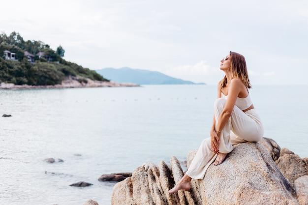 Portret van jonge kalme gelukkig kaukasische fit slanke vrouw in crop cami top en broek set zit alleen op rotsachtig tropisch strand bij zonsondergang