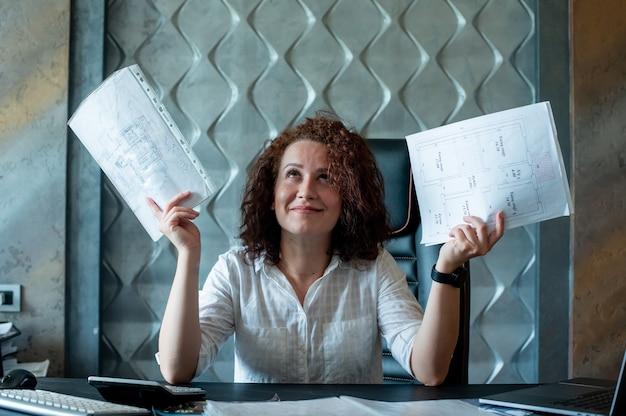 Portret van jonge kantoor werknemer vrouw zittend aan een bureau met documenten opzoeken verhogen handen glimlachen op zoek verward werken in kantoor