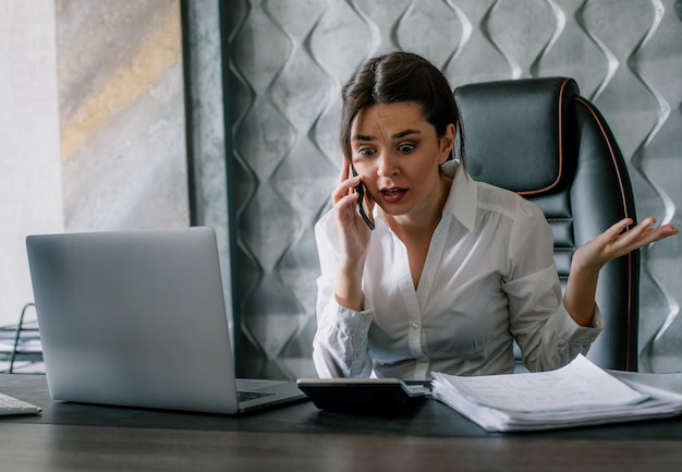 Portret van jonge kantoormedewerker vrouw zit op bureau met documenten praten op mobiele telefoon met boze uitdrukking gefrustreerd nerveus en gestrest werken op kantoor