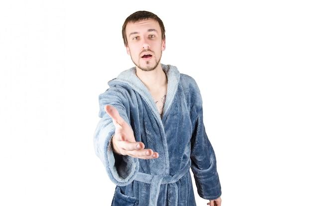 Portret van jonge kaukasische bebaarde man in blauwe badjas uitnodigen om te komen geïsoleerd op een witte achtergrond