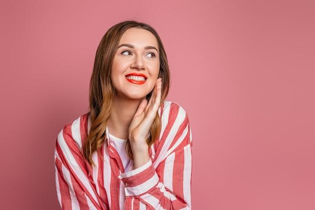 Portret van jonge kaukasische bruinharige vrouw met rode lippen die gestreept rood overhemd dragen dat en naar de kant glimlacht kijkt die op roze muur wordt geïsoleerd.