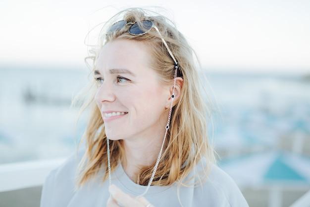 Portret van jonge kaukasische lachende lachende meisje vrouw in zonnebril buiten op de achtergrond van het strand.