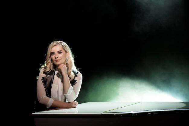 Portret van jonge kaukasische vrouw die zich dichtbij de grote piano bevindt