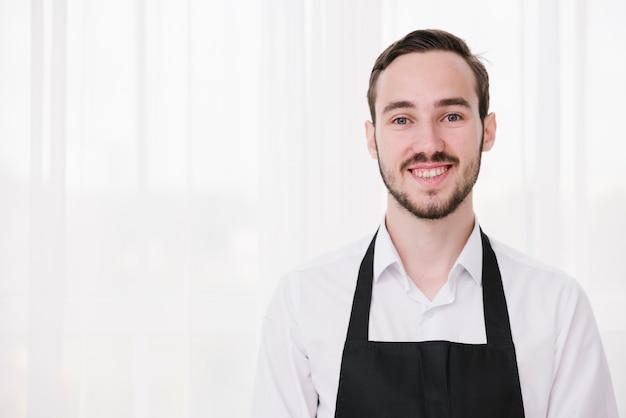 Portret van jonge kelner die camera bekijkt