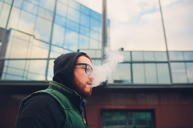 Portret van jonge kerel met grote baard in glazen die een elektronische sigaret tegenover stedelijke achtergrond vaping.