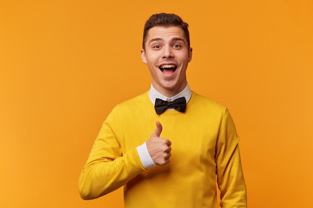 Portret van jonge knappe aantrekkelijke man netjes gekleed in gele trui over wit overhemd met strikje, heeft opgewonden gezichtsuitdrukking