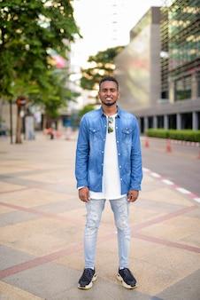 Portret van jonge knappe afrikaanse bebaarde man met afro haar het verkennen van de straten van de stad buiten