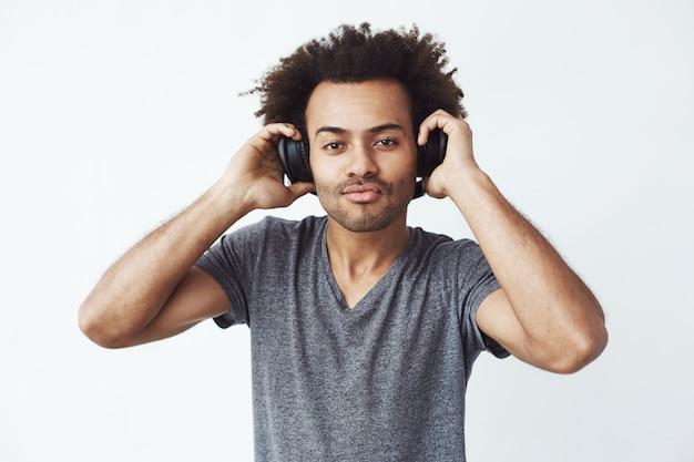 Portret van jonge knappe afrikaanse man luisteren naar muziek