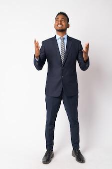 Portret van jonge knappe afrikaanse zakenman die kostuum tegen witte muur draagt
