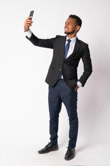 Portret van jonge knappe afrikaanse zakenman in pak tegen witte muur