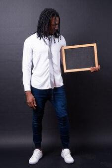 Portret van jonge knappe afrikaanse zakenman met dreadlocks op zwart