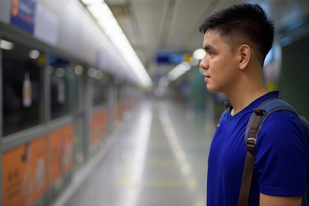 Portret van jonge knappe aziatische toeristenmens die op de trein bij mrt-metrostation in bangkok, thailand wachten