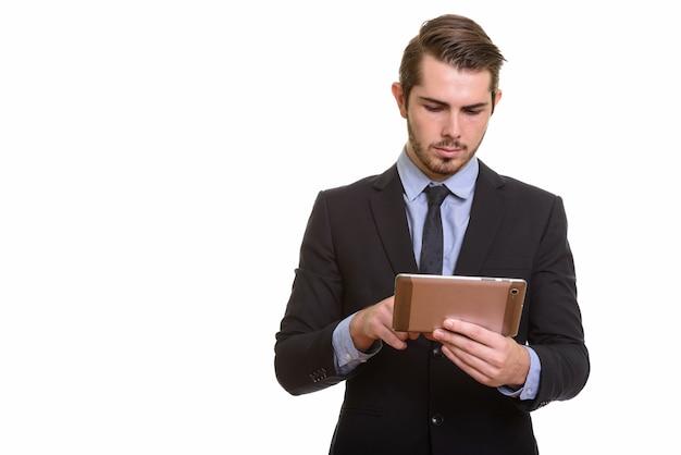 Portret van jonge knappe bebaarde zakenman in pak met behulp van digitale tablet