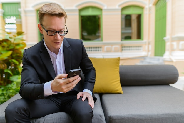 Portret van jonge knappe blonde zakenman in pak ontspannen in de coffeeshop buitenshuis