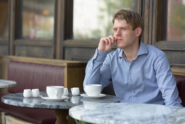Portret van jonge knappe blonde zakenman ontspannen in de coffeeshop buitenshuis