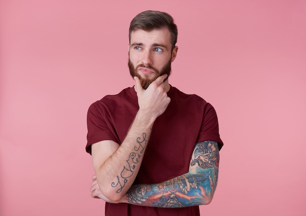 Portret van jonge knappe denken getatoeëerde rode bebaarde man in rood t-shirt, kijkt weg en raakt de kin, staat op roze achtergrond.