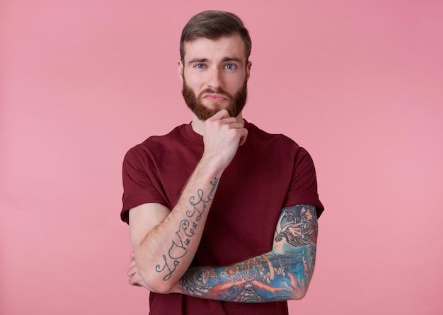 Portret van jonge knappe denken getatoeëerde rode bebaarde man in rood t-shirt, raakt de kin, staat op roze achtergrond kijkt naar de camera.