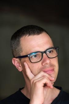 Portret van jonge knappe ernstige zwartharige zelfverzekerde succesvolle intellectuele man in glazen.
