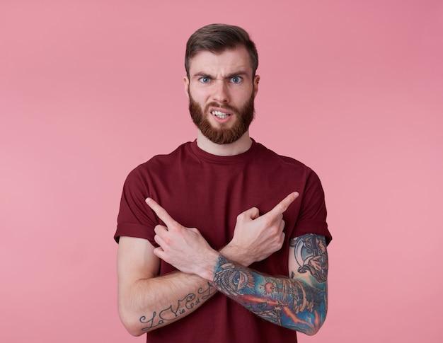 Portret van jonge knappe fronsende misverstand rode bebaarde man in rood t-shirt, staat over roze achtergrond kijkt naar de camera met walging en wijst in verschillende richtingen.