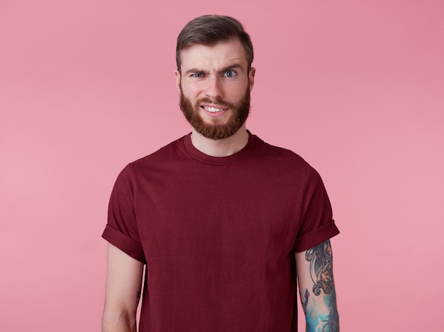 Portret van jonge knappe fronsende misverstand rode bebaarde man in rood t-shirt, staat over roze achtergrond kijkt naar de camera met walging.