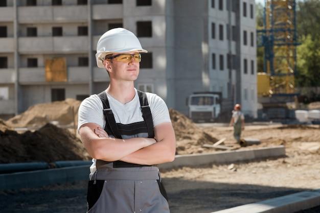 Portret van jonge knappe harde arbeider die witte beschermende helm dragen en overall werken bij concstructionplaats