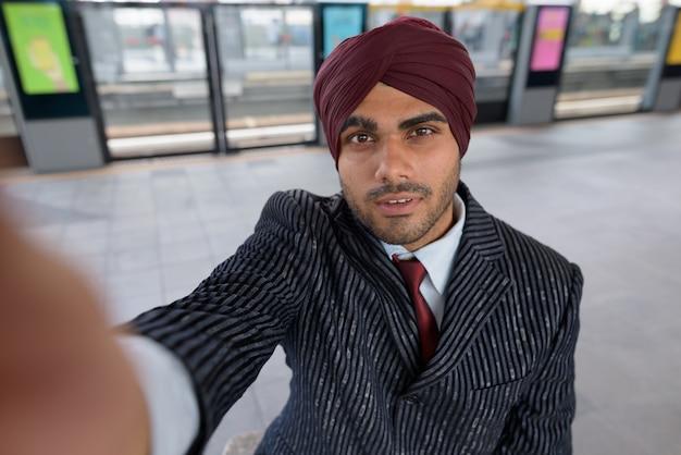 Portret van jonge knappe indiase sikh zakenman tulband dragen tijdens het verkennen van de stad bangkok, thailand